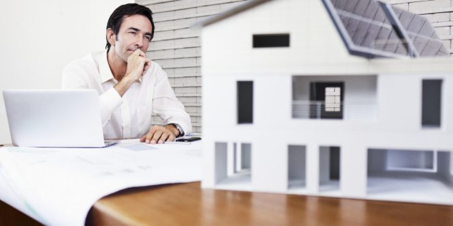 Architect sitting at office desk with blueprint and laptop looking at house mock-up