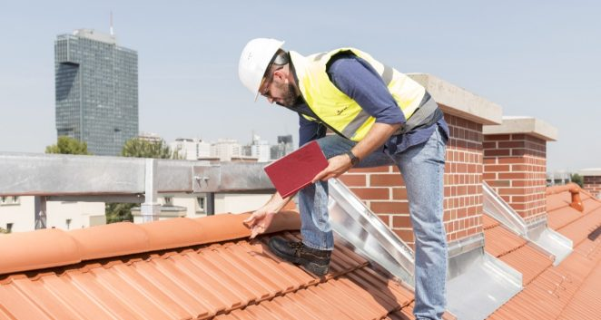 Urban roofers builder standing on roof checking toof tiles wearing hard hat and safety jacket